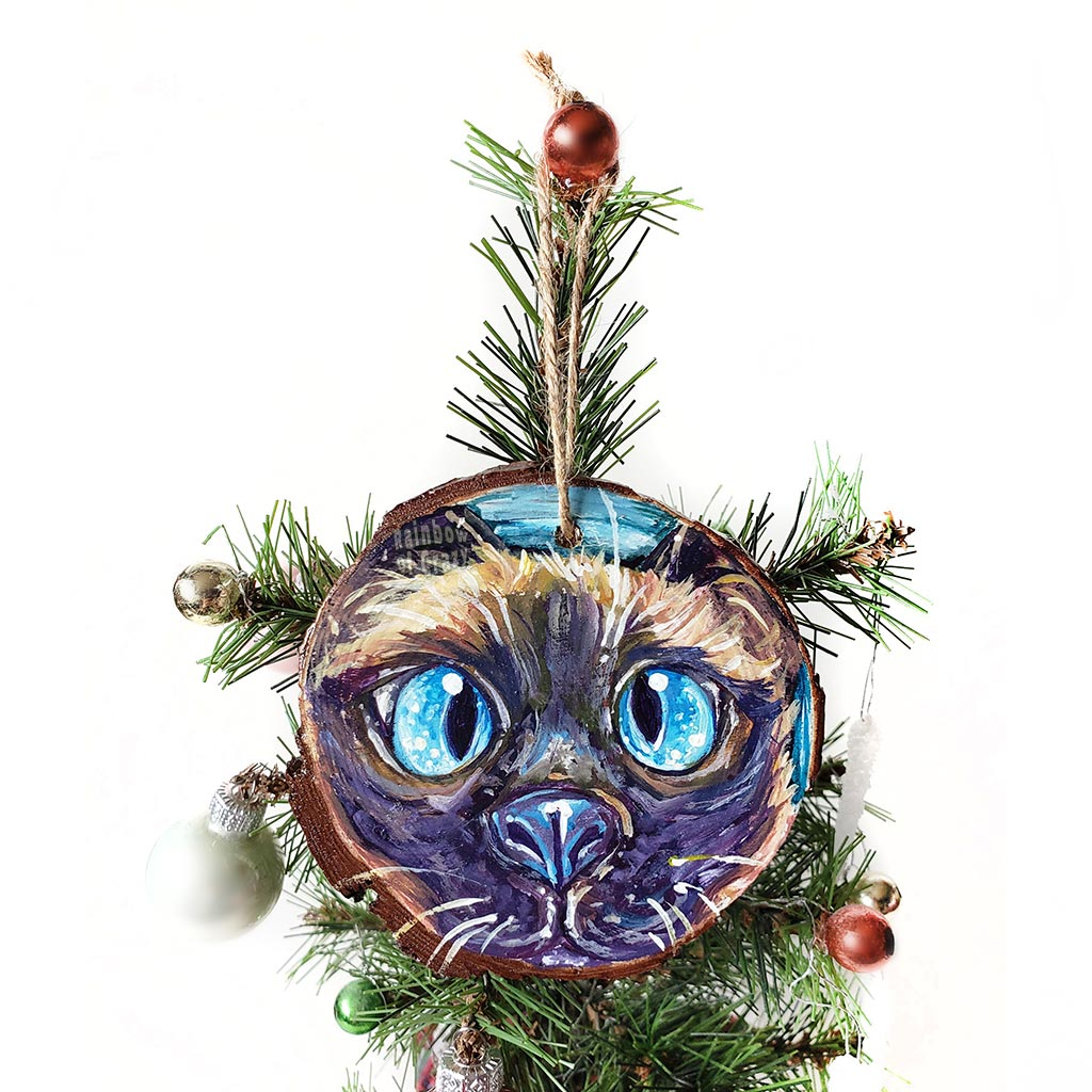 A hand painted wood ornament with artwork of the face of a blue eyed siamese cat