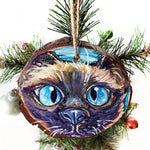 A wood ornament with a hand painted portrait of a siamese cat with blue eyes