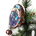A Christmas ornament with a painting fo a blue eyed Siamese cat's face
