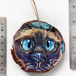 A Christmas ornament with a painting fo a blue eyed Siamese cat's face, next to two rulers to show its size: 2 15/16 x 3 1/8 inches or 7.8 x 8.4 cm