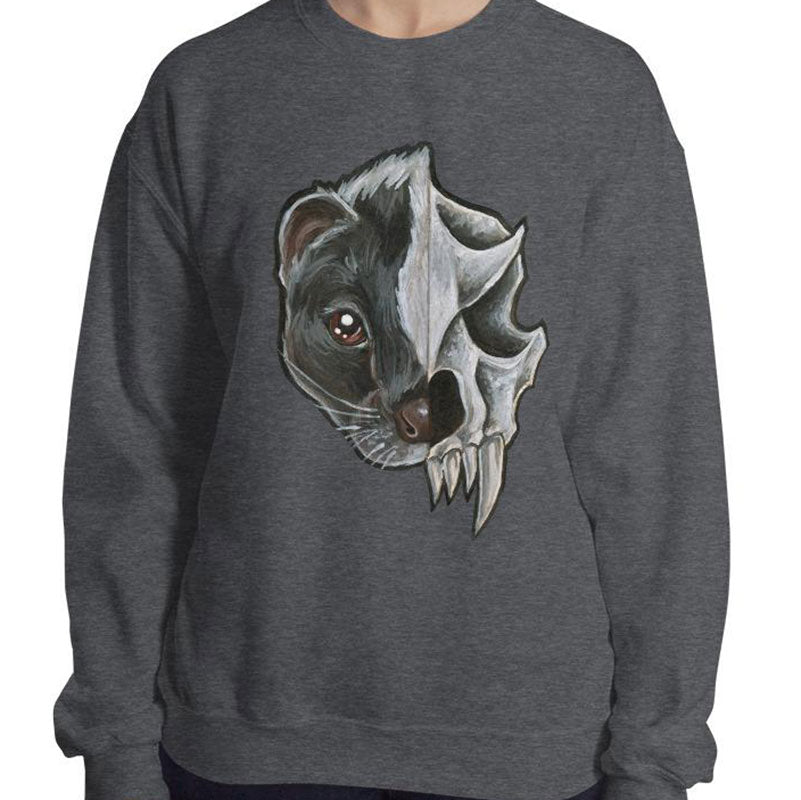 A woman wears a unisex sweatshirt in the colour dark heather grey, printed with a graphic of a split portrait: the left side features the face of a skunk, and the right side features an evil looking skunk skull