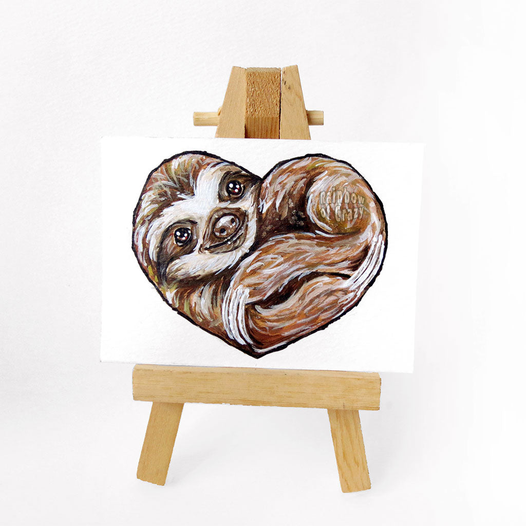 An ACEO sized painting of a sloth, curled up in the shape of a heart.