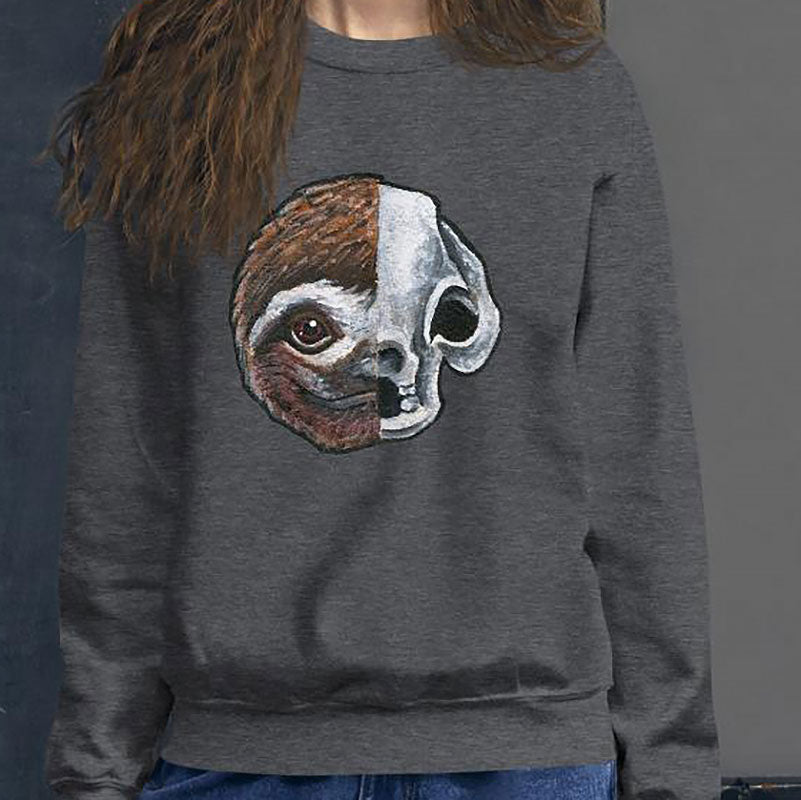 A woman wears a unisex sweatshirt in the colour dark heather grey, printed with a graphic of a split image: the left side features a sloth's face, and the right side features an evil looking sloth skull.