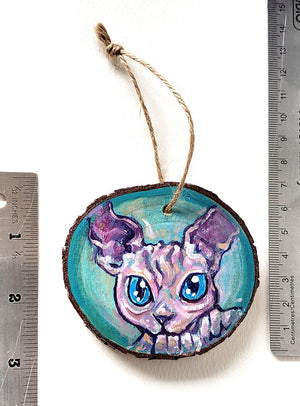 A handmade Christmas tree wood ornament, featuring a painting of a sphynx cat with blue eyes