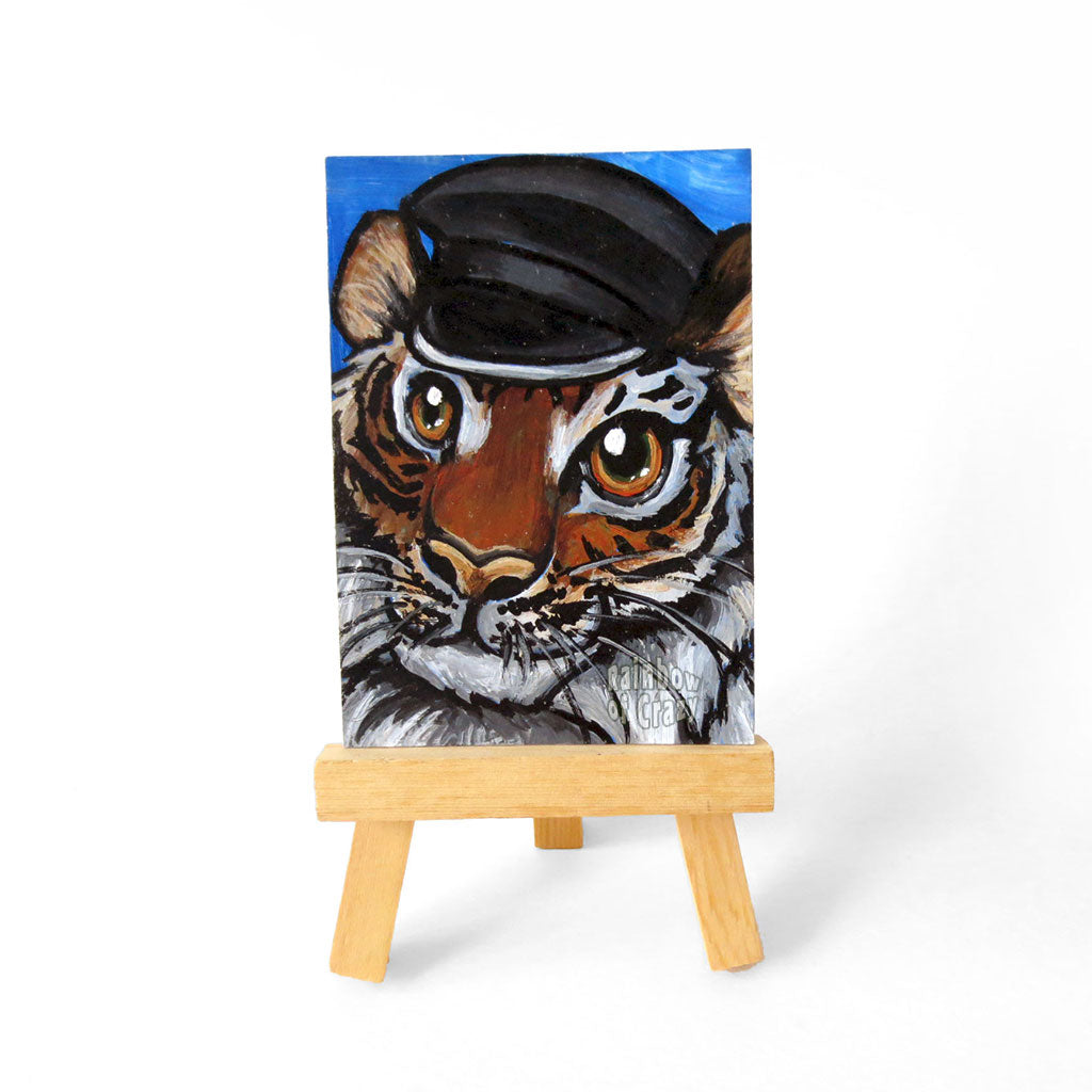 "A tiger with a black leather hat, is painted on an ACEO, or ""Art Cards Editions and Originals"", which measures 2.5"" x 3.5"" (6.35 cm x 8.89 cm)"