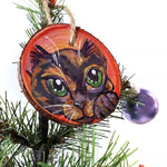 A wood Christmas tree ornament, hand painted with art of a tortoiseshell cat, with green eyes, in front of a red and pink background