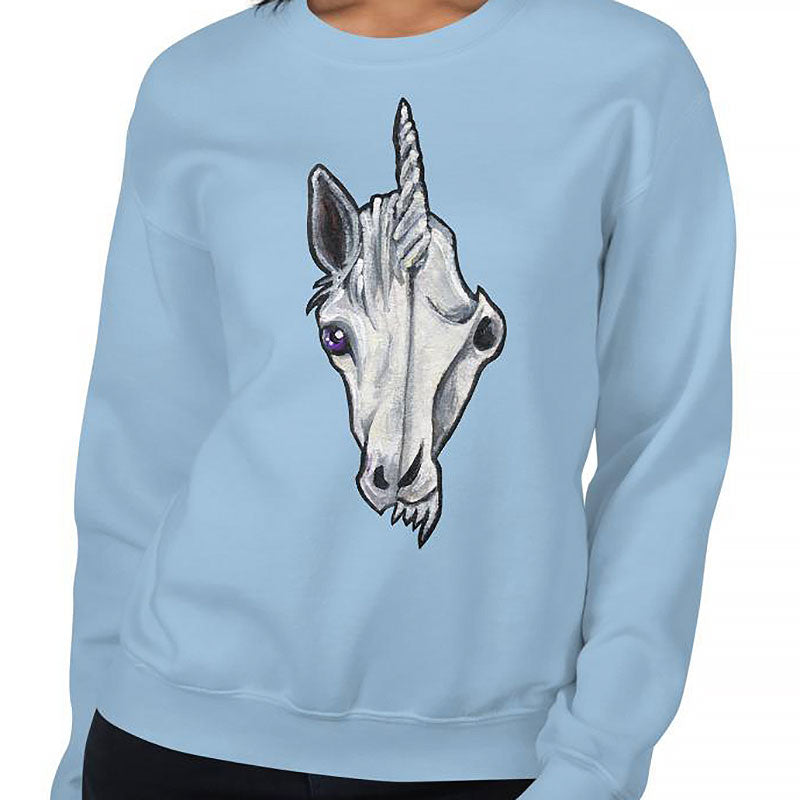 A woman is wearing a unisex sweatshirt in the colour light blue, which is printed with a split graphic: the left side features the face of a unicorn, and the right side features an evil looking skull