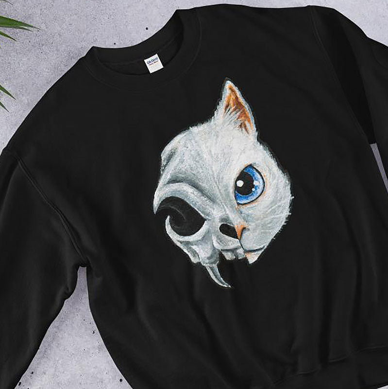 A unisex sweatshirt in the colour black, printed with art split into two: the right side features the face of a blue eyed white cat, and the left side features an evil looking cat skull.