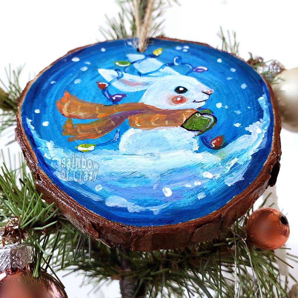 A wood Christmas ornament, hand painted with a white rabbit sitting on the snow with a blue background, with an orange scarf, green mittens, and christmas lights on its ears