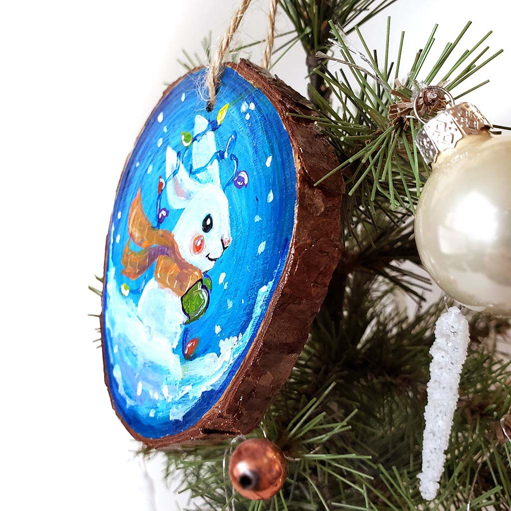 A wood Christmas ornament, hand painted with a white bunny rabbit sitting on the snow with a blue background, with an orange scarf, green mittens, and christmas lights on its ears