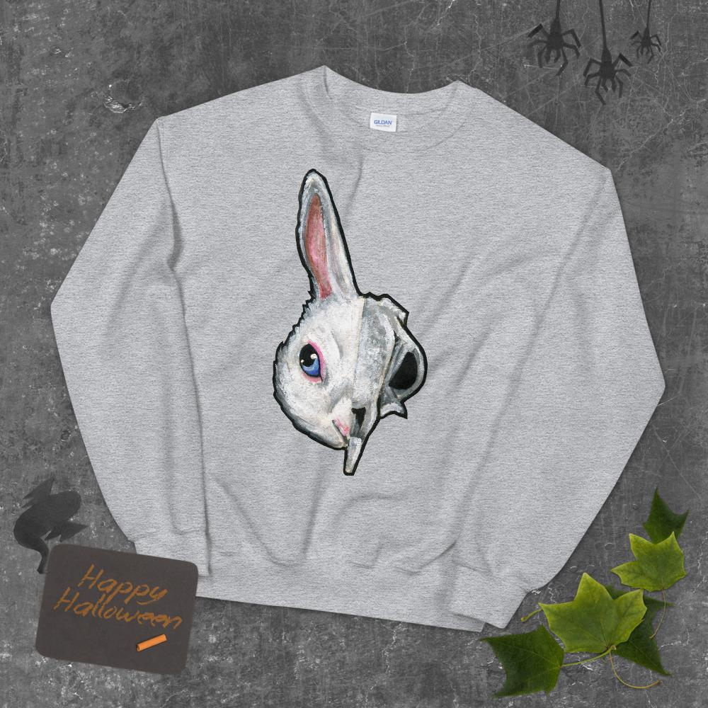 A unisex sweatshirt in the colour sport grey, printed with art of a split image: the left side features a white rabbit's face, and the right side features a scary looking rabbit skull