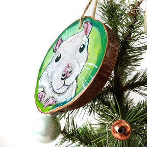 A Christmas wood ornament, hand painted with art of a white fancy rat, in front of a green background