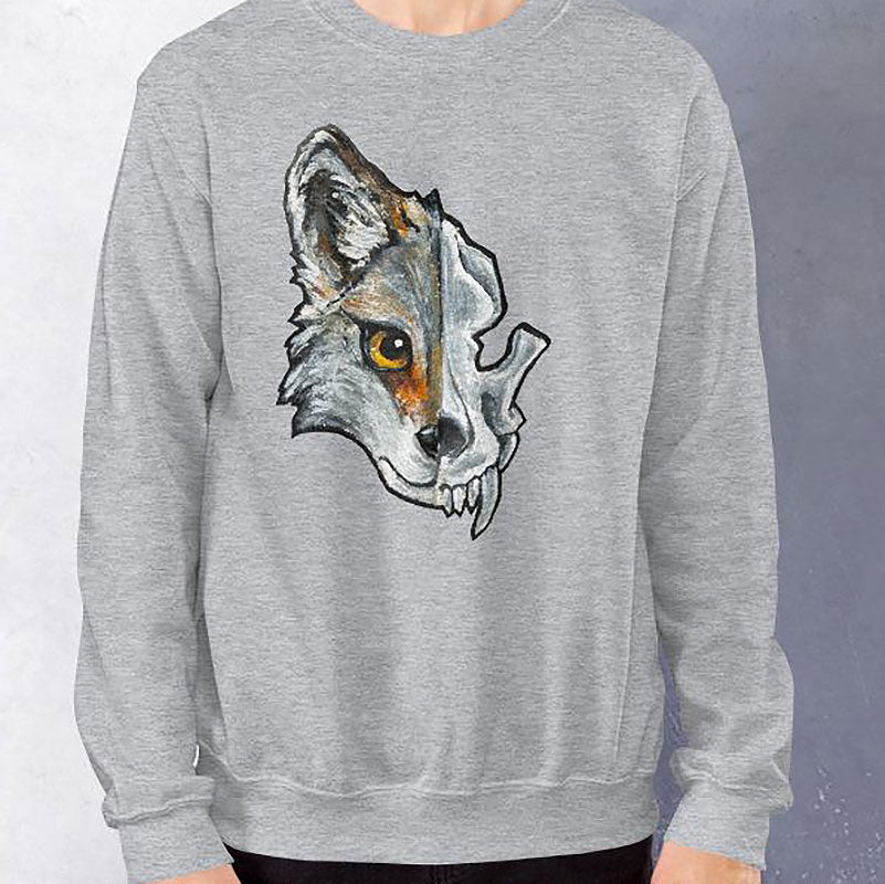 A man wears a unisex sweatshirt in the colour sport grey, printed with a graphic of a split image: the left side features a wolf's face, and the right side features an evil looking wolf skull.