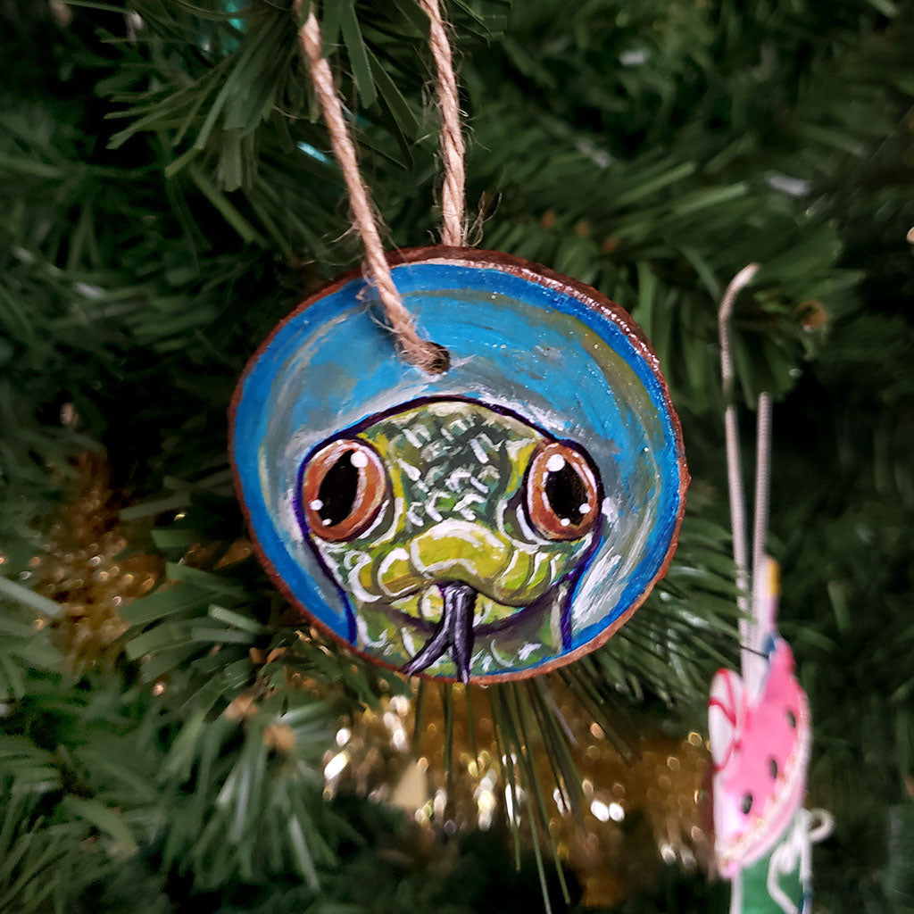 A tree ornament, hand painted with art of a yellow anaconda snake