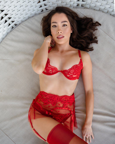 Asian woman in red lingerie laying on sun bed