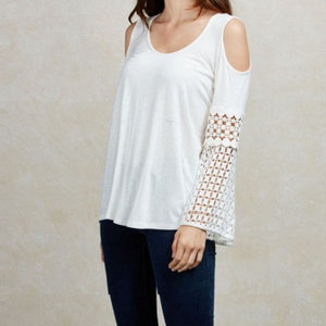 The Natasha top is a white relaxed fit cold shoulder top with crochet detailed sleeves.