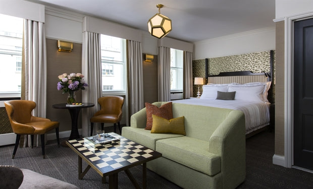The Academy Hotel, London - hotel room with neutral colors, green sofa, checkerboard coffee table, and bed
