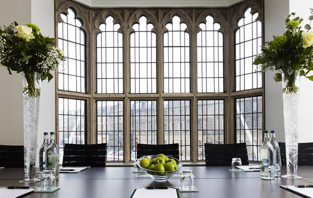 The Glasshouse, Edinburgh - hotel conference room with dark wood table, flower vases, and large gothic windows