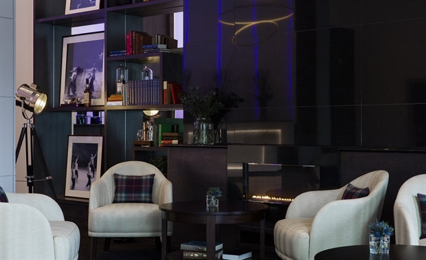 The Glasshouse, Edinburgh - hotel lounge with dark wood furniture, white armchairs, and purple light