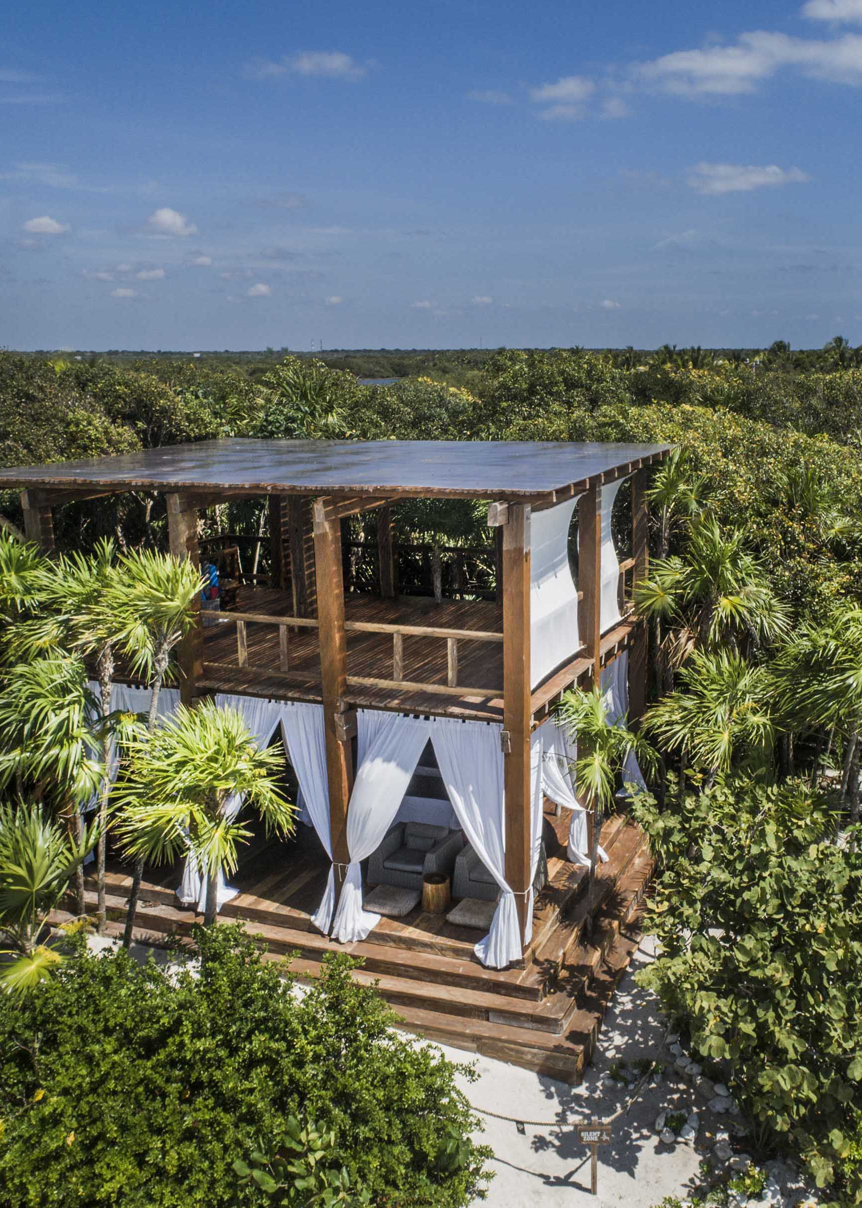 Jashita Hotel, Tulum - wooden two story open air patio with white curtains in a jungle landscape