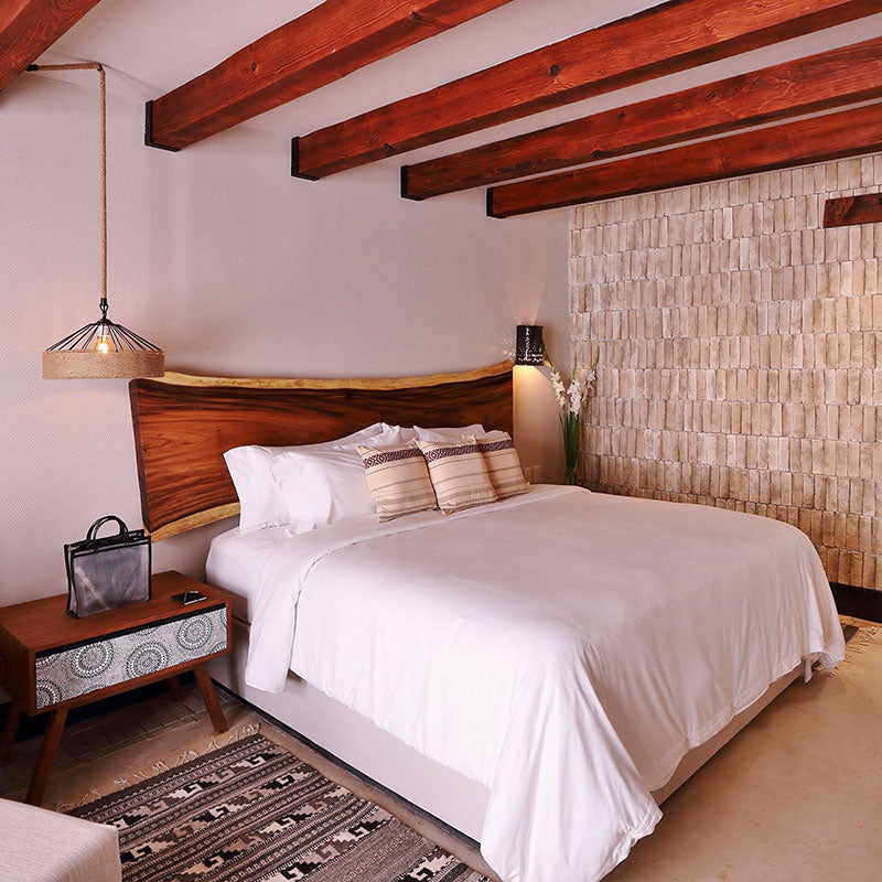 Amomoxtli, Tepoztlán - hotel room with wooden beam ceiling, queen size bed, and wooden bedside table.