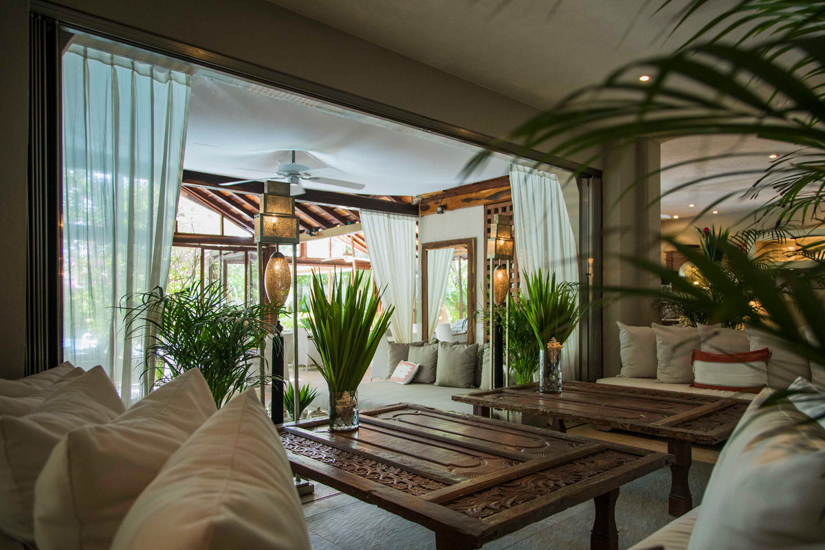 Jashita Hotel, Tulum - open air patio with couches, intricately carved coffee tables, woven lamps, and large sliding doors