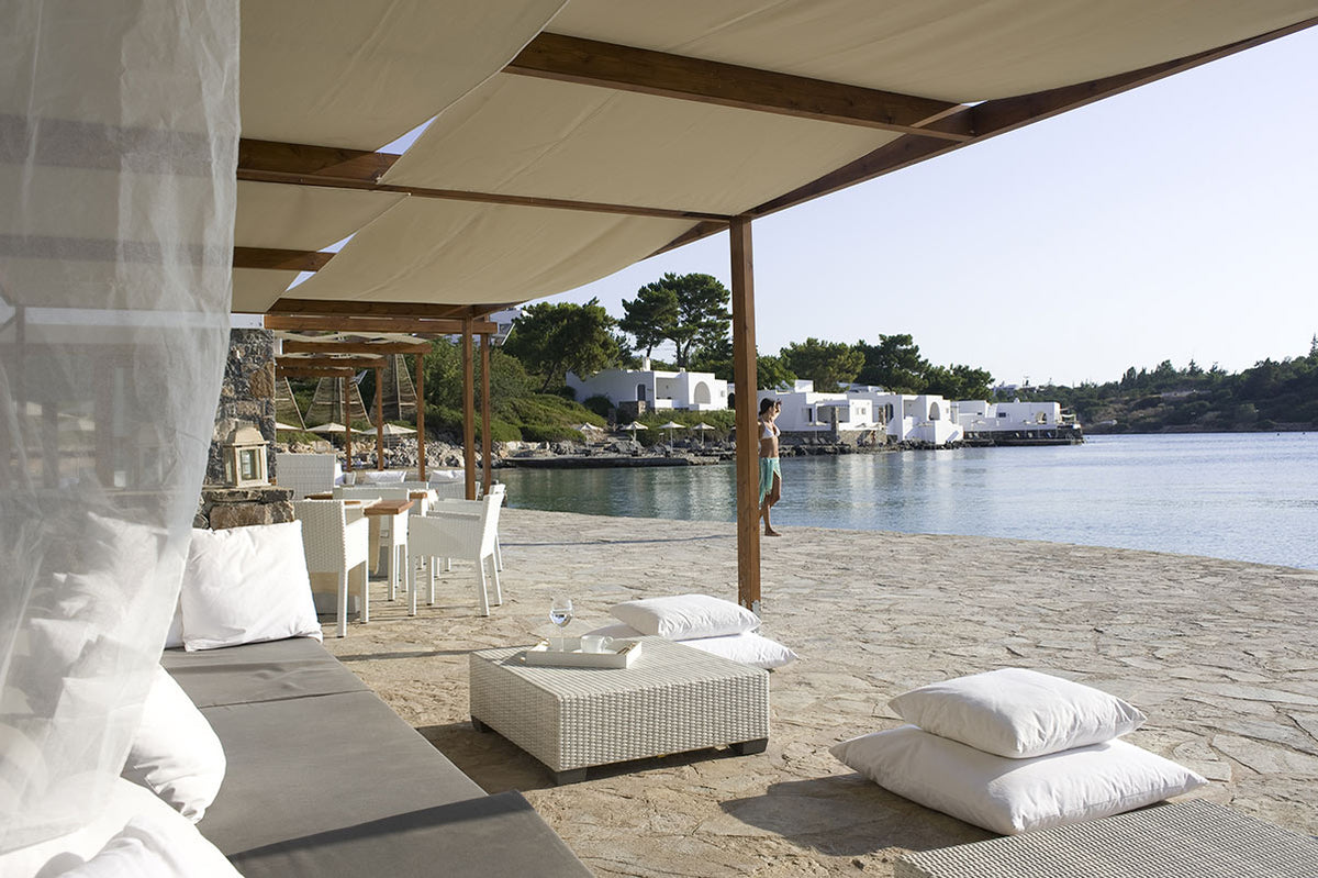Minos Beach Art Hotel, Crete - chic patio with lounge chairs, lounge beds, and couches under a woven tarp awning overlooking ocean
