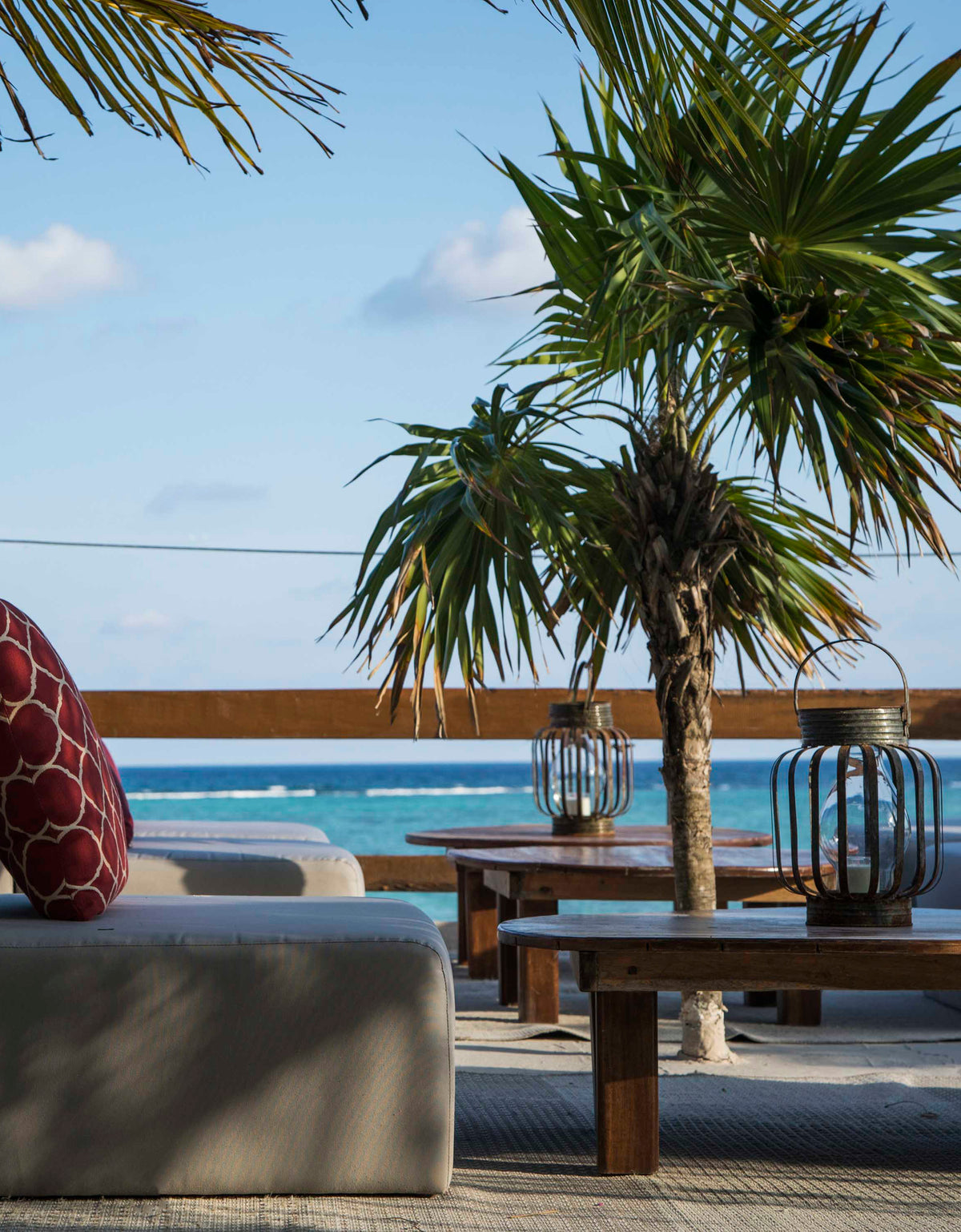 Jashita Hotel, Tulum - patio with sofas, wicker lanterns, coffee tables, small palm trees, and an ocean view