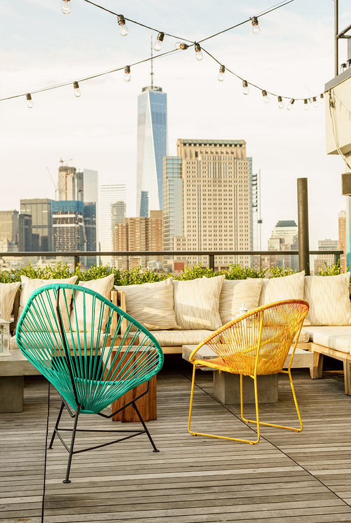Hotel Hugo, NYC - rooftop lounge with wicker chairs, a large couch, hanging string lights, and a city view
