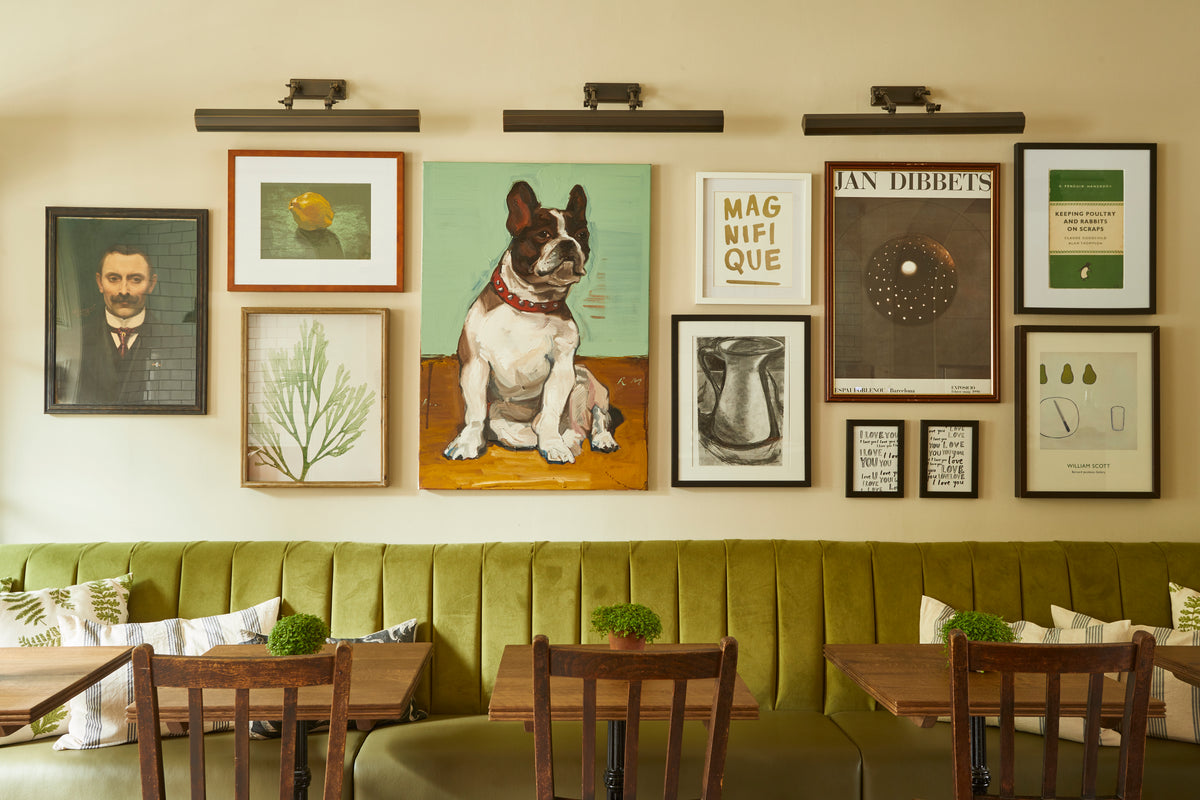 Lime Tree Hotel, London, UK - The Buttery hotel restaurant with green booth seats, brown wood tables and chairs, and gallery wall of art