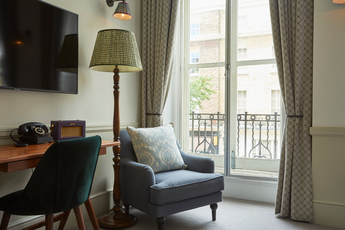 Lime Tree Hotel, London, UK - hotel room with desk, chair, armchair, and window with balcony overlooking Belgravia