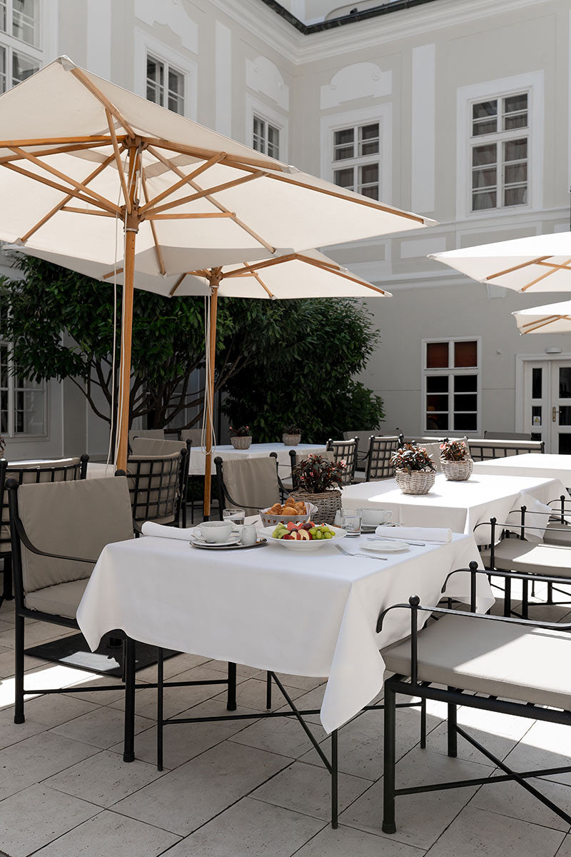 Smetana Hotel, Prague - stone patio with dining tables, chairs, and white sun umbrellas