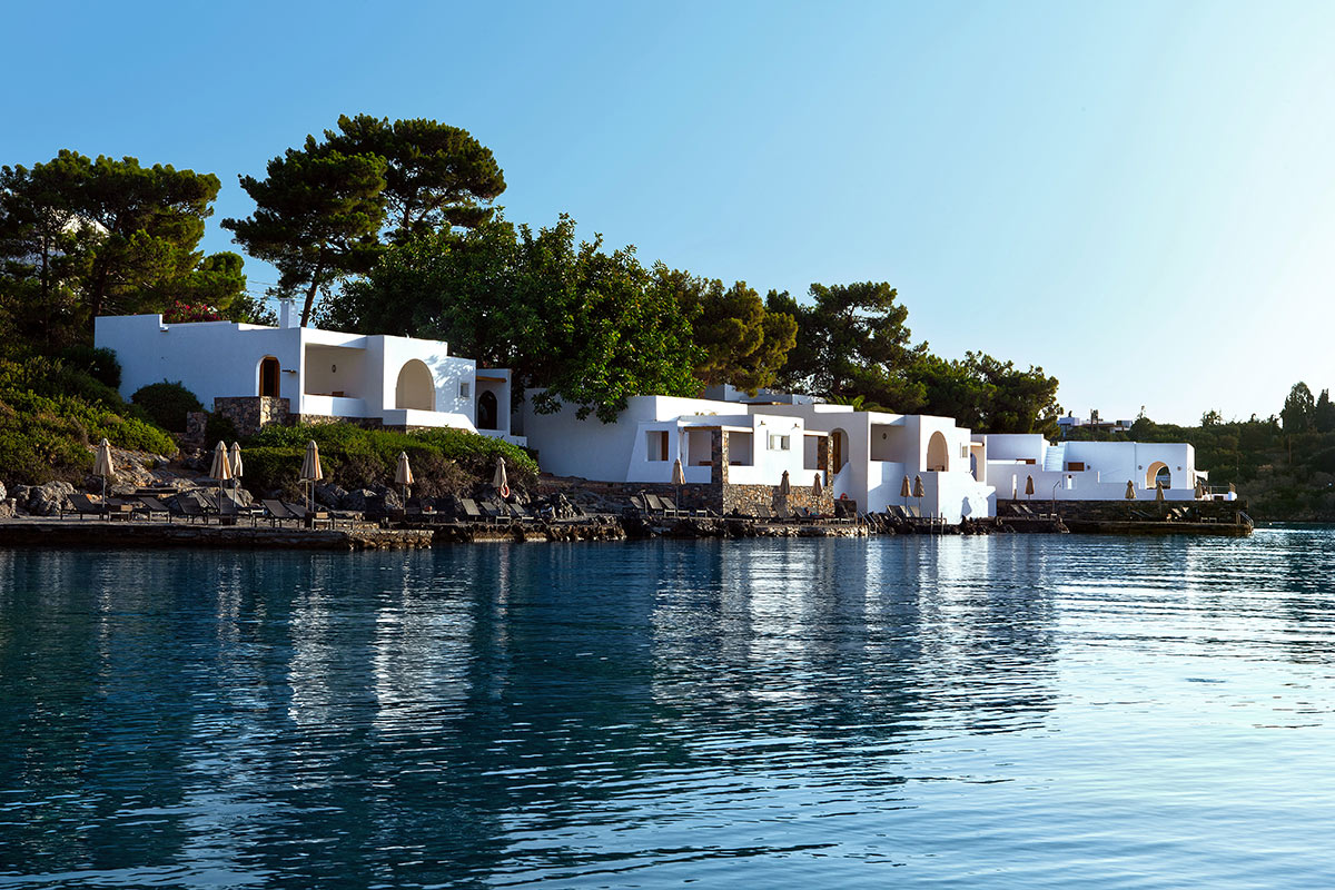 Minos Beach Art Hotel, Crete - white Greek villas and patio with lounge chairs overlooking calm blue water