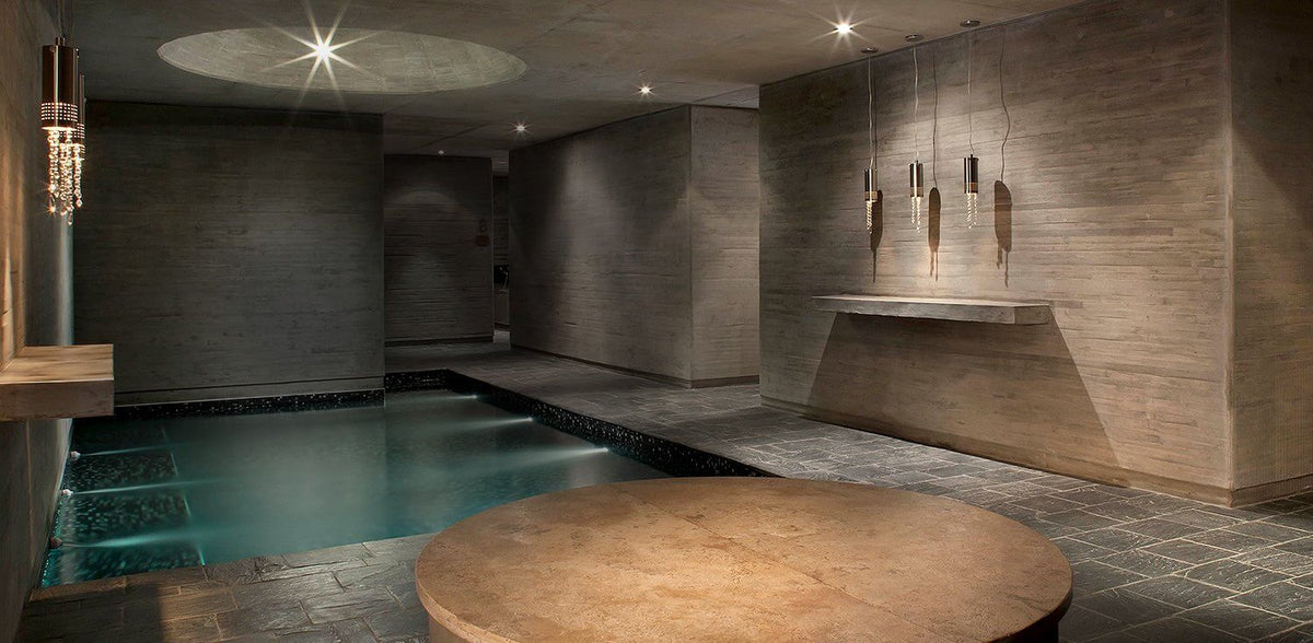 Entre Cielos, Mendoza - indoor hotel pool in dark stone room with light fixture decoration