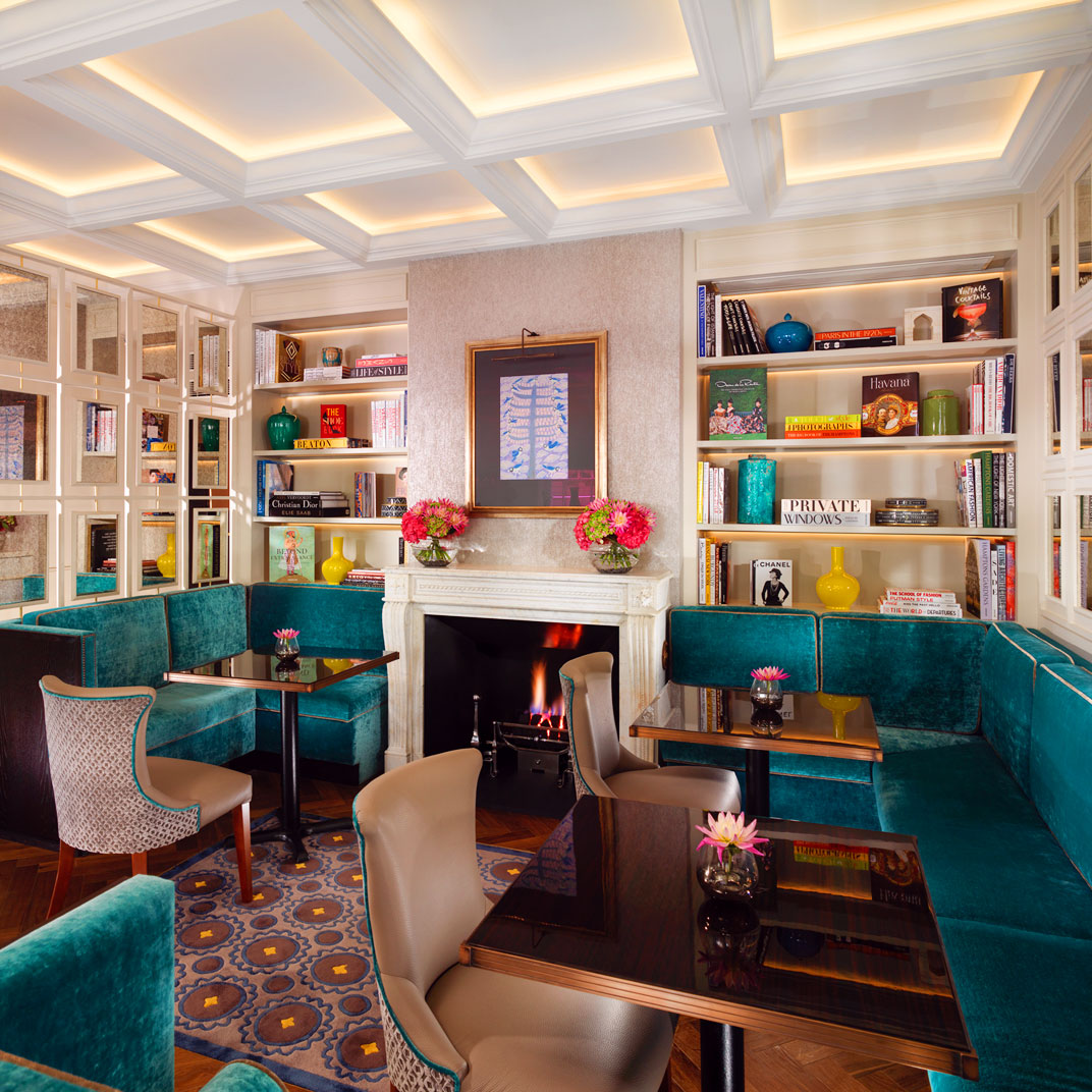 Flemings Mayfair, London - vintage hotel lounge with teal couches, dark wood tables, and library wall bookshelves