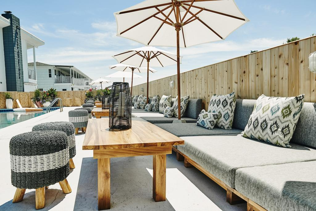 Hero Beach Club, Montauk - hotel pool with grey couches, birch tables, and white sun umbrellas