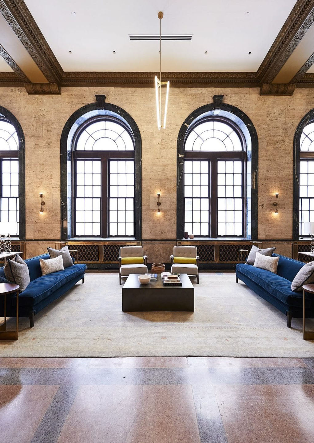 Noelle, Nashville - classic hotel lobby with dark wood details, large rounded windows, and blue couches