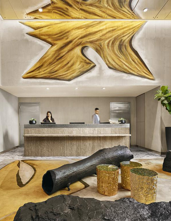 Mondrian Park Avenue, NYC - contemporary hotel lobby with gold and black logs, stone reception desk, and two employees behind the counter