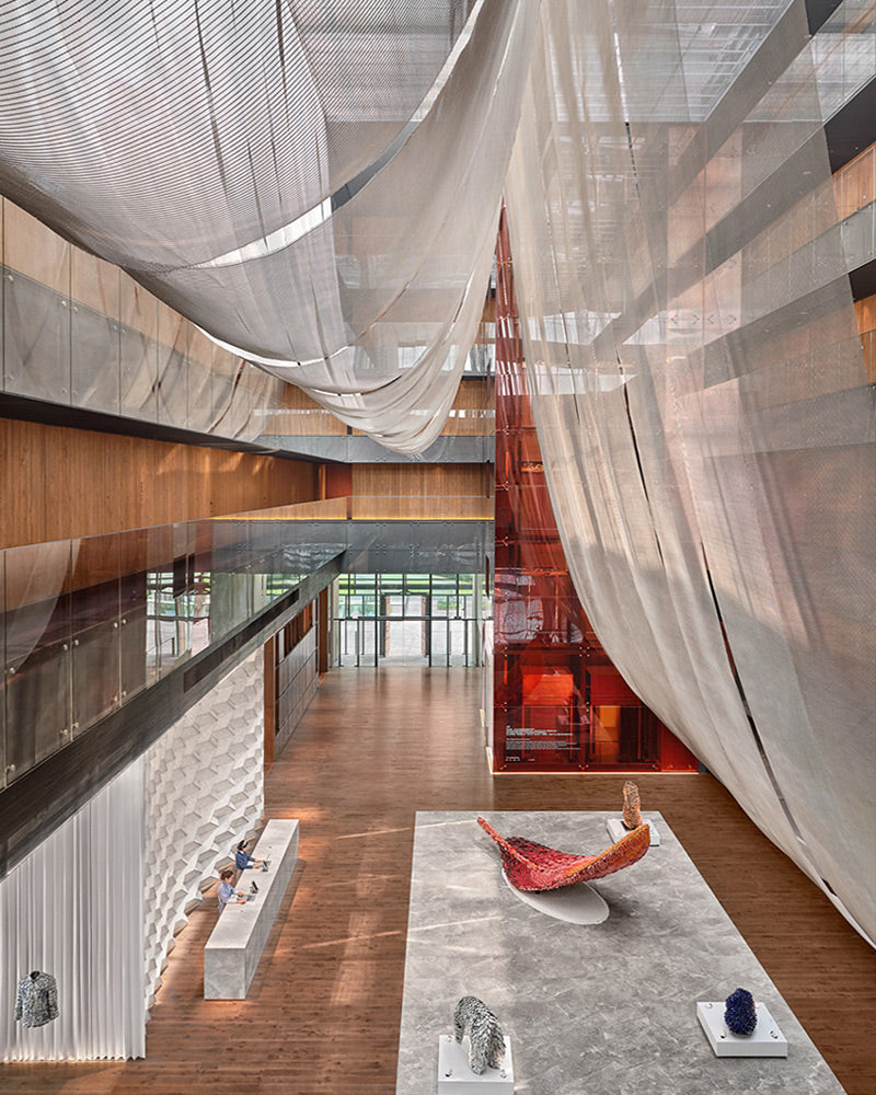 The Opposite House, Beijing - spacious hotel lobby with art installations, balconies, and grey drapes from the ceiling