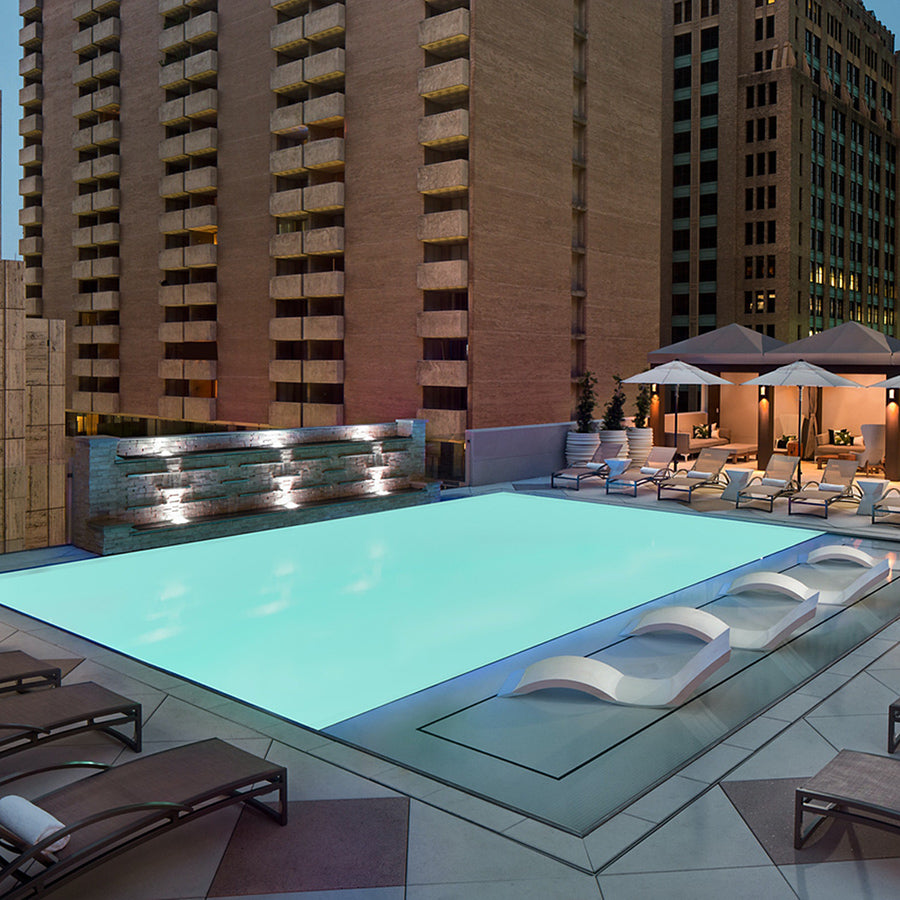 The Adolphus Hotel, Dallas - rooftop pool with in-pool seats, lounge chairs, sun umbrellas, and a view of Dallas at night