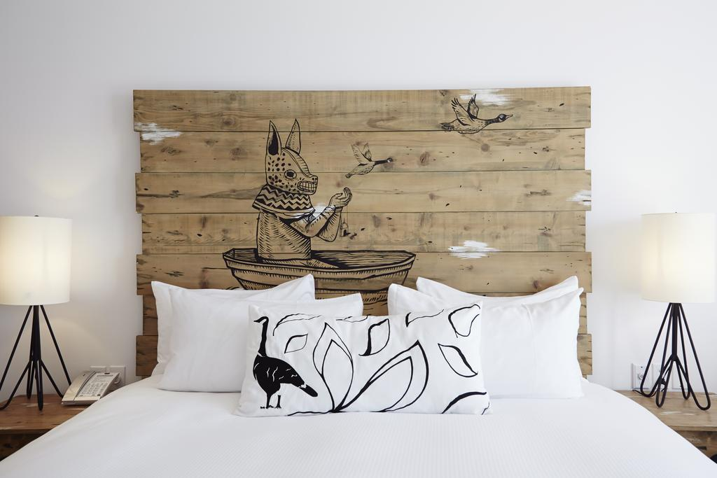 Hotel El Ganzo, Los Cabos - hotel room bed with white duvet, rustic wooden headboard with painted design, and a goose design pillow