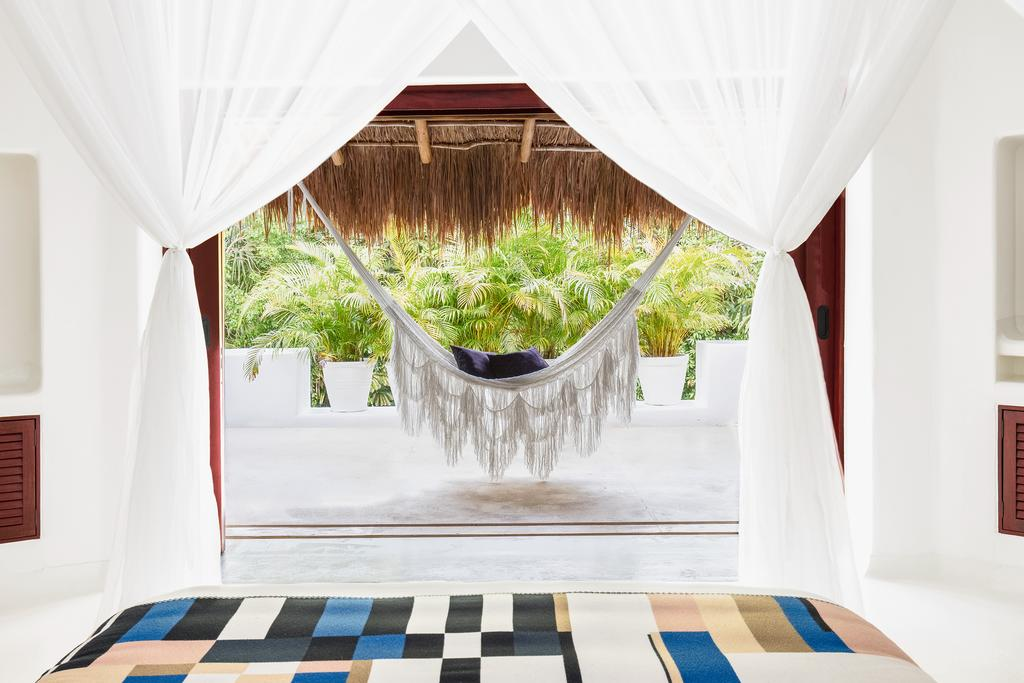 Hotel Esencia, Xpu-Ha - view of hotel room from canopy bed looking onto private patio with thatch roof, hammock, and jungle view