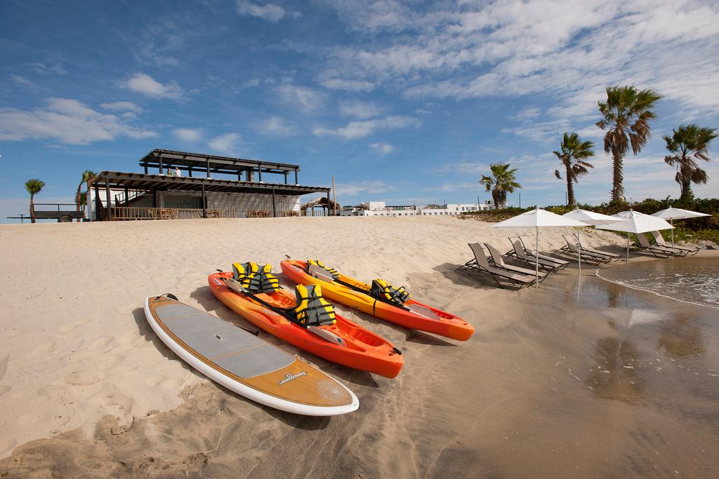 Hotel El Ganzo, Los Cabos - beach with lounge chairs, sun umbrellas, kayaks, and a paddle board