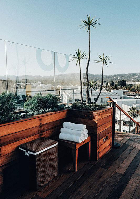 Sixty Beverly Hills, Los Angeles - rooftop patio with white towels on a stool and a hamper with views of city