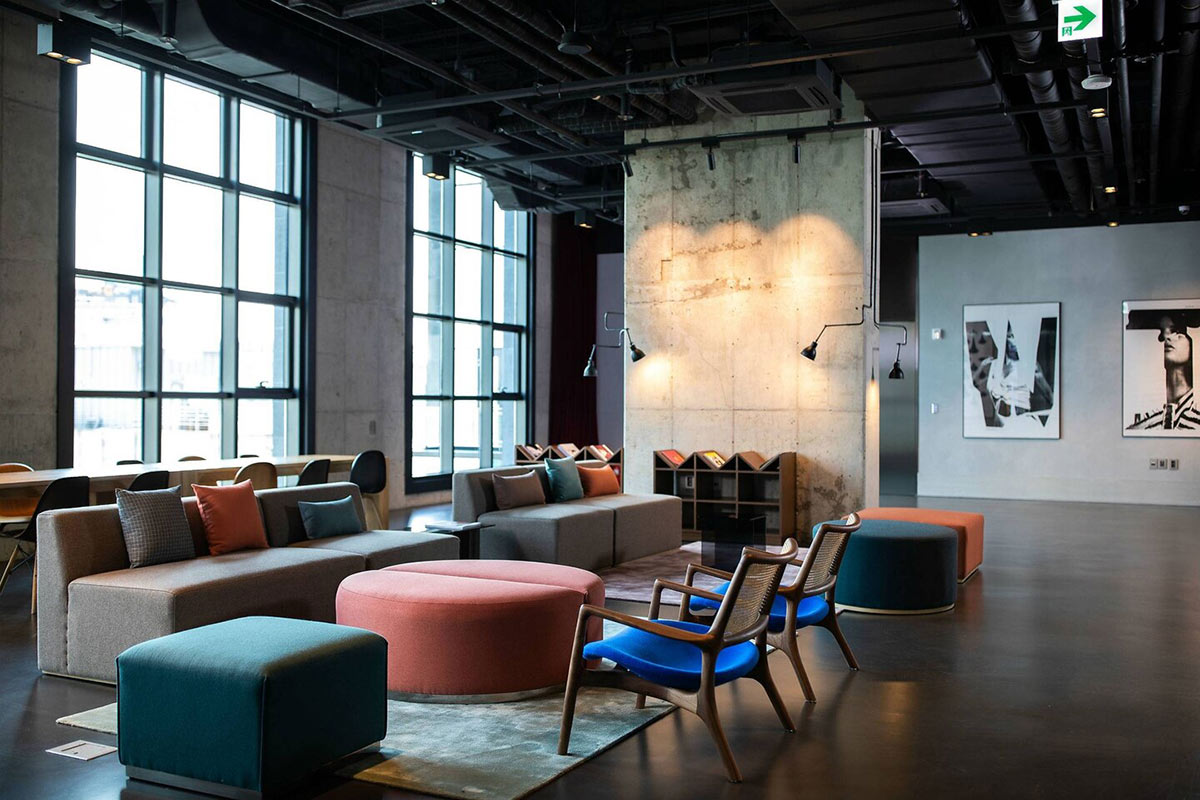 RYSE, Seoul - hotel lounge with concrete floors and walls, grey, sage, and orange furniture, and photography art on the walls