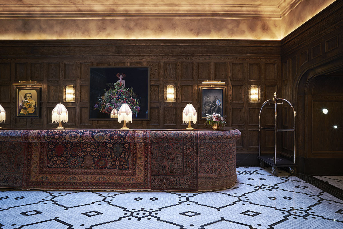 The Beekman, NYC - hotel lobby with wood walls, tiled floors, and intricate carpet reception desk