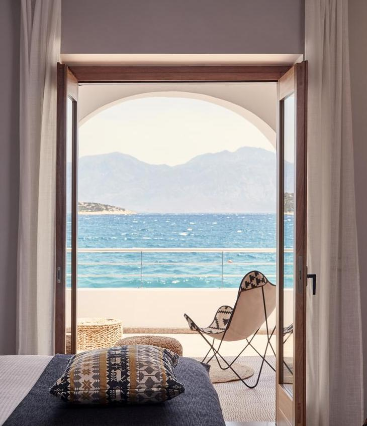 Minos Beach Art Hotel, Crete - hotel room with open doors overlooking private balcony and Aegean sea