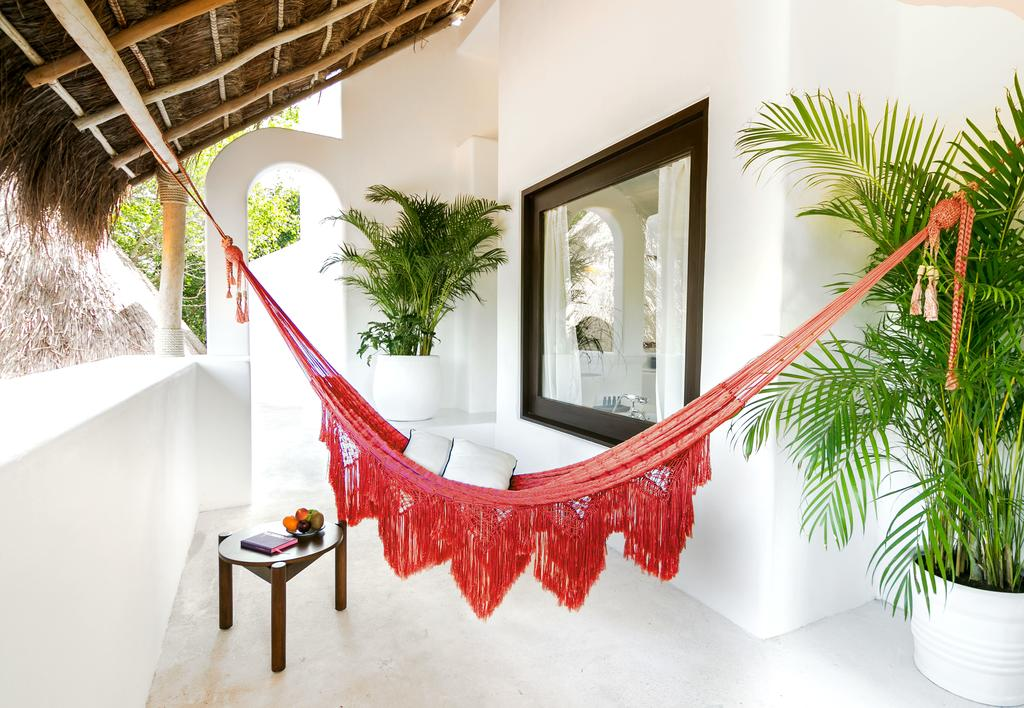 Hotel Esencia, Xpu-Ha - all-white balcony with thatch roof, potted palm trees, and red macramé hammock