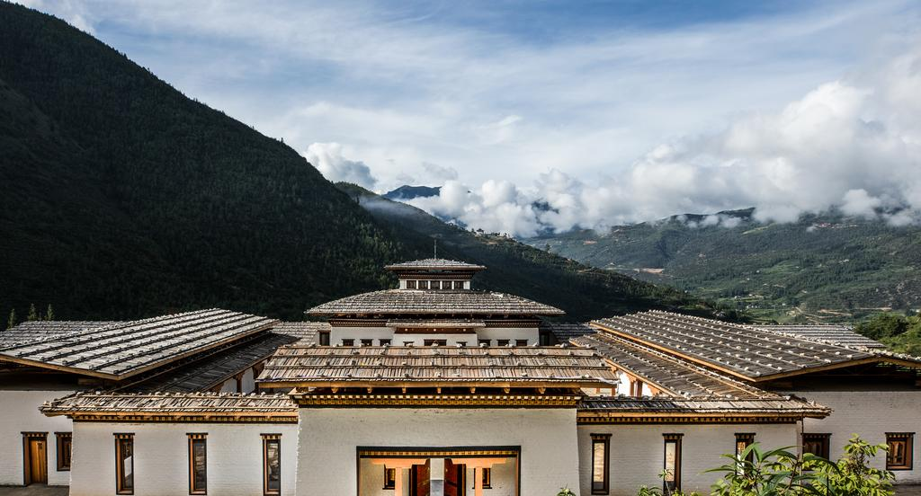 Bhutan Spirit Sanctuary, Bhutan - exterior of hotel, large white building with thatch roof at the foot of a mountain