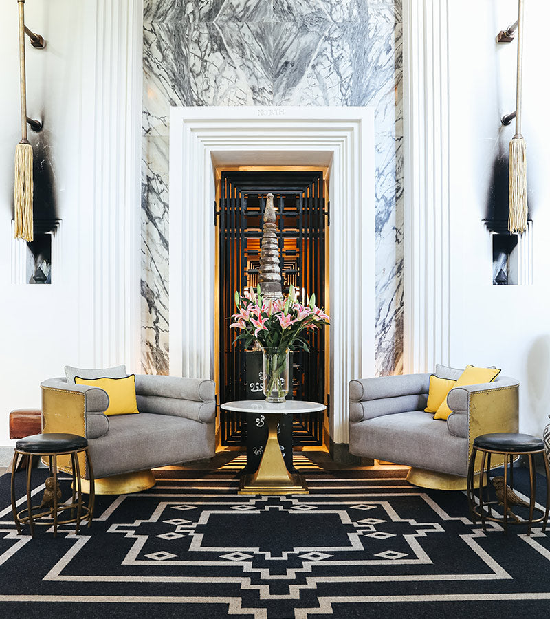Bensley Collection Shinta Mani, Siem Reap - lobby with intricate square carpet and grey armchairs